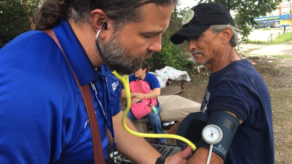 Physician assistant takes the blood pressure of a homeless encampment resident