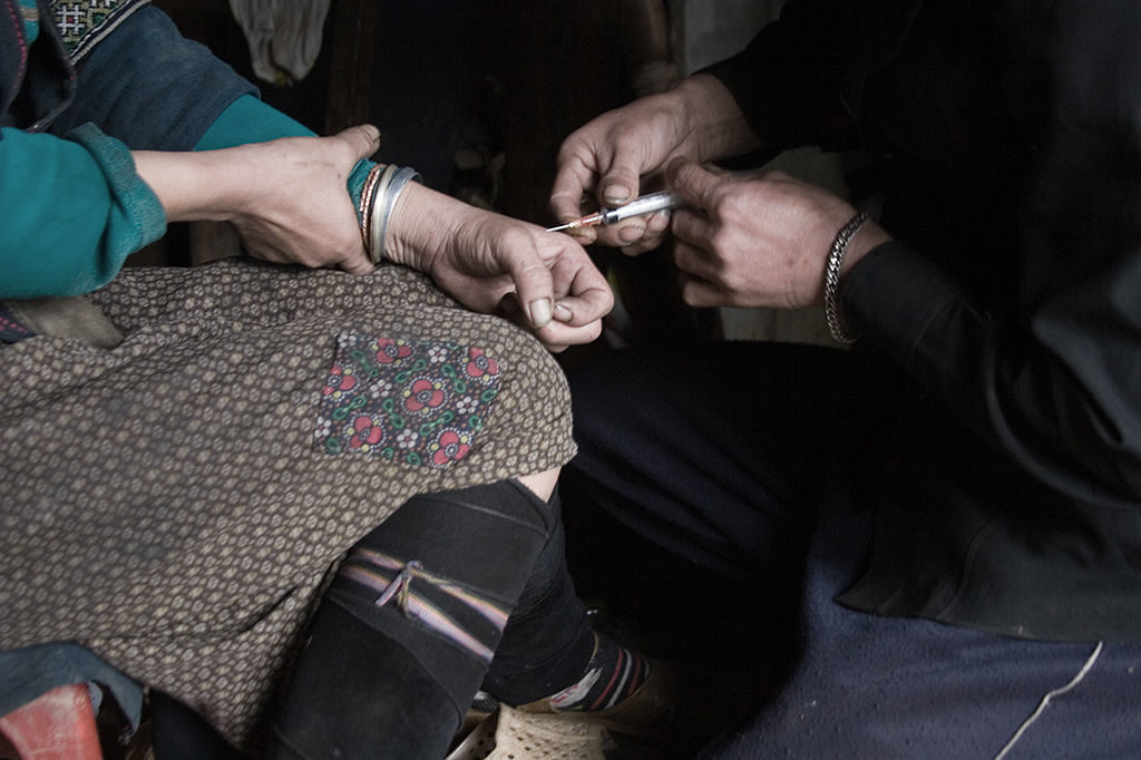 a man injects heroin into the hand of a another