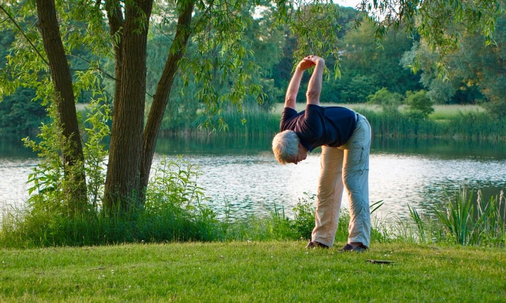 Older white haired man stretches by a lake.