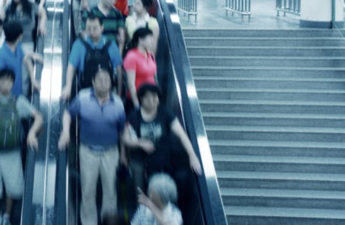 People riding the escalator next to empty stairs