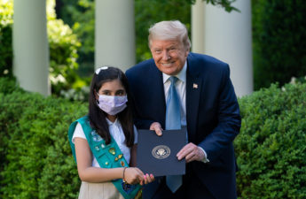President Trump poses without a face mask with a Girl Scout who is.