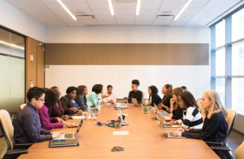 A group of businesswomen in discussion around conference table.