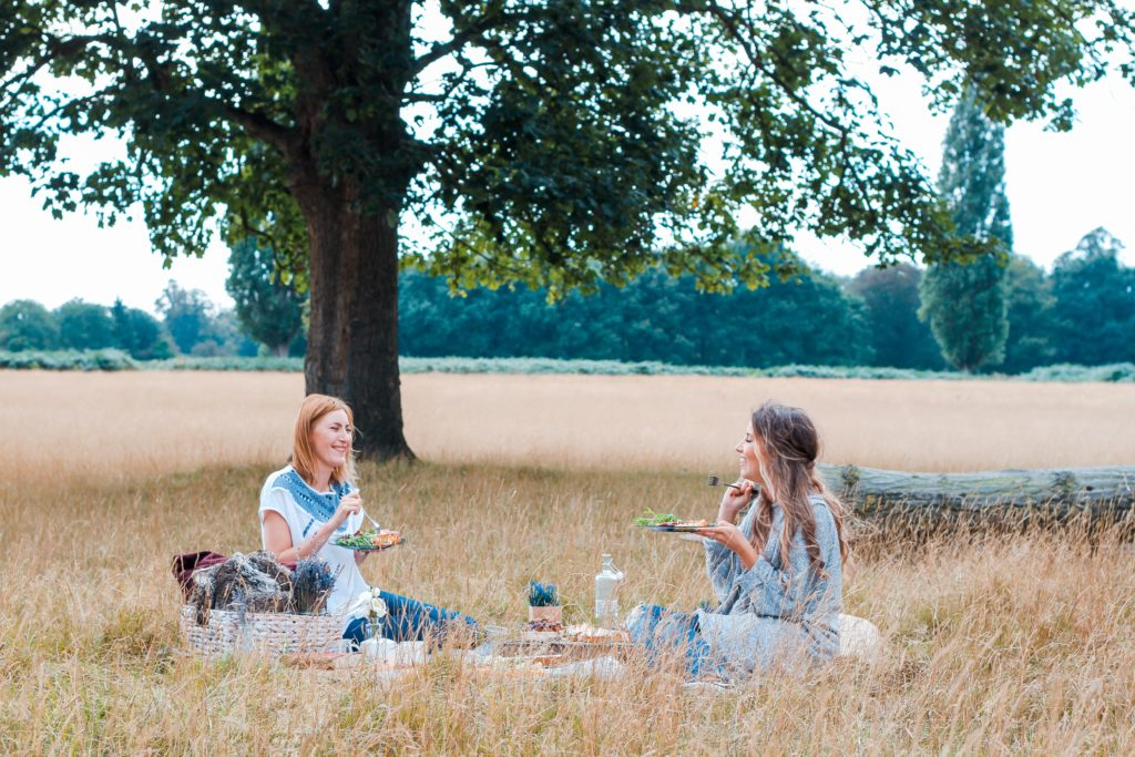 Two women in a field enjoying a picnic