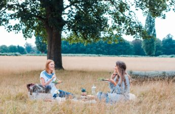 Two women in a field enjoying a picnic