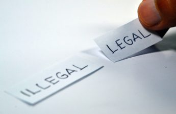 """Two strips of paper: One says """"legal,"""" the other """"illegal."""""""