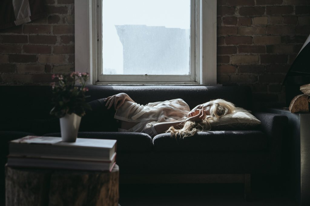 woman sleeping on a sofa in a darkened room