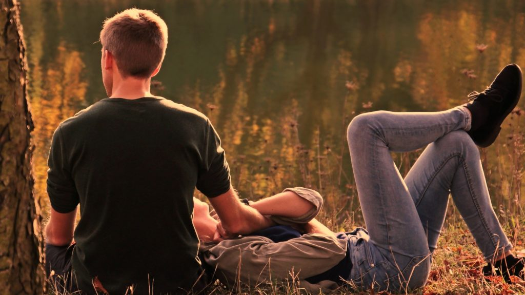 A couple relaxes outdoors in late afternoon light.