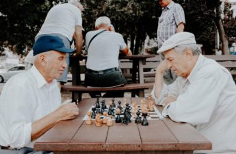 Two older men playing chess outside on a table in a park.